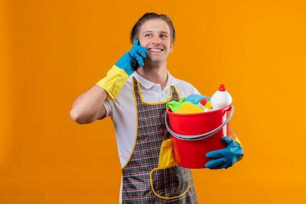 Junger hansdome-mann, der schürze und gummihandschuhe trägt, die eimer mit reinigungswerkzeugen halten, die fröhlich lächeln, während sie auf handy sprechen, das über orange wand steht
