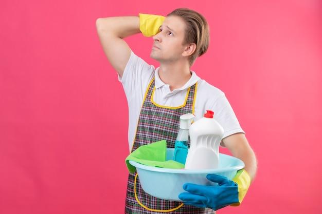 Junger hansdome-mann, der schürze und gummihandschuhe trägt, die eimer mit reinigungswerkzeugen halten, die mit nachdenklichem ausdruck auf gesicht denkend stehen und über rosa wand stehen