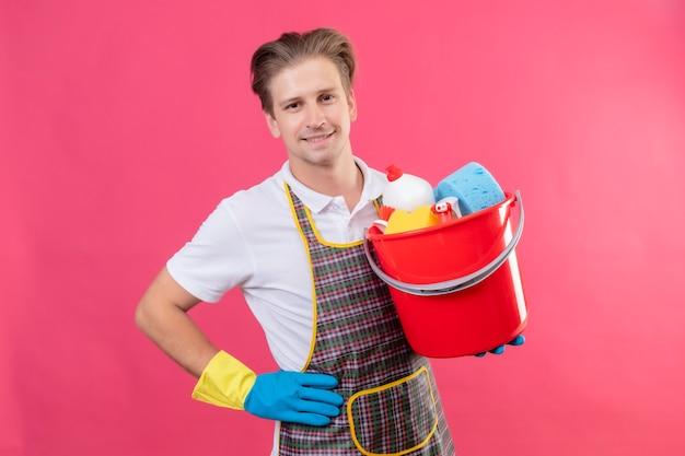 Junger hansdome-mann, der schürze und gummihandschuhe trägt, die eimer mit reinigungswerkzeugen mit dem selbstbewussten lächeln auf gesicht halten, das über rosa wand steht