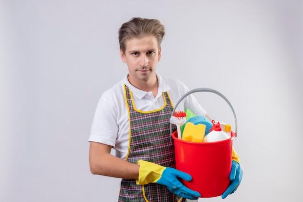 Junger hansdome-mann, der schürze und gummihandschuhe trägt, die eimer mit reinigungswerkzeugen mit sicherem lächeln auf gesicht halten, das über weißer wand 2 steht