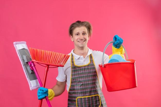 Junger hansdome-mann, der schürze und gummihandschuhe trägt, die eimer mit reinigungswerkzeugen und mopp halten, der camear verwirrt lächelnd über rosa wand betrachtet