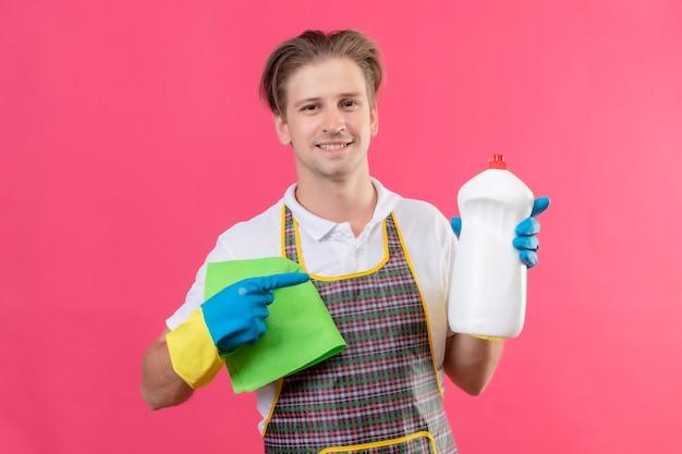 Junger hansdome-mann, der schürze und gummihandschuhe trägt, die flasche mit reinigungsmitteln und teppich halten, die zuversichtlich lächelnd über rosa wand stehen