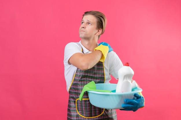 Junger hansdome-mann, der schürze und gummihandschuhe trägt, die haltebecken mit reinigungswerkzeugen halten, die seine schulter berühren, die schmerzen haben, die über rosa wand stehen