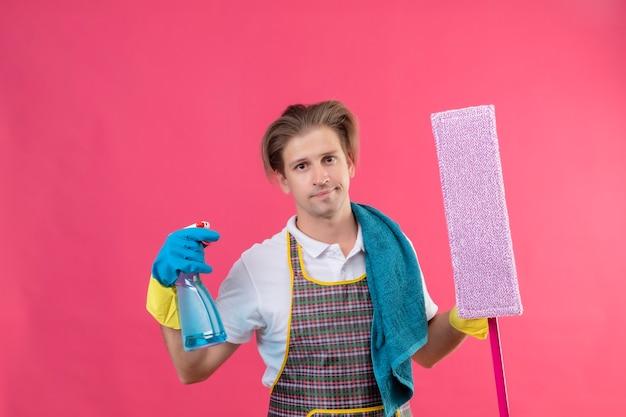 Junger hansdome-mann, der schürze und gummihandschuhe trägt, die reinigungsspray und mopp mit skeptischem lächeln auf gesicht halten, das über rosa wand steht
