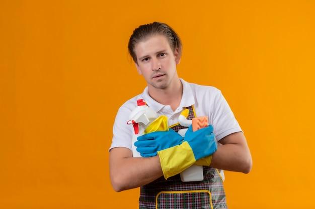Junger hansdome-mann, der schürze und gummihandschuhe trägt, die reinigungswerkzeuge halten
