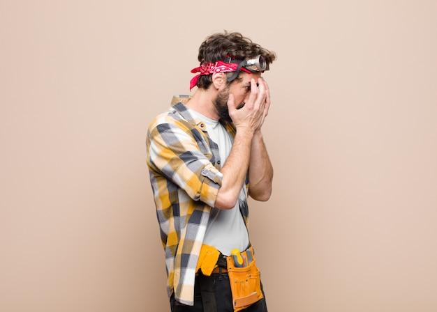 Junger haushälterin, der augen mit händen mit einem traurigen, frustrierten ausdruck der verzweiflung bedeckt, weinend, seitenansicht gegen flache wand
