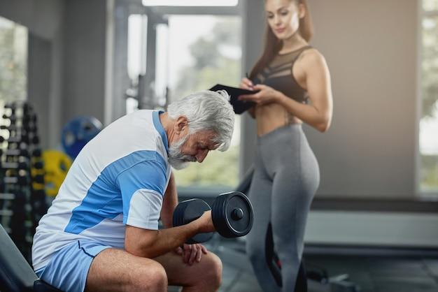 Junger heißer weiblicher persönlicher trainer, der älteren grauen mann stützt.