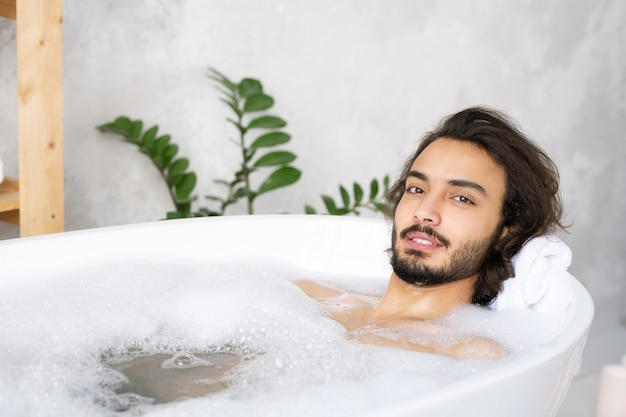 Junger heiterer bärtiger mann, der sich entspannt, während er im bad mit heißem wasser und schaum vor kamera liegt
