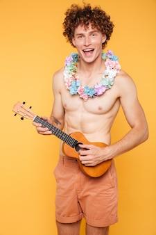 Junger hemdloser kerl, der ukulele hält