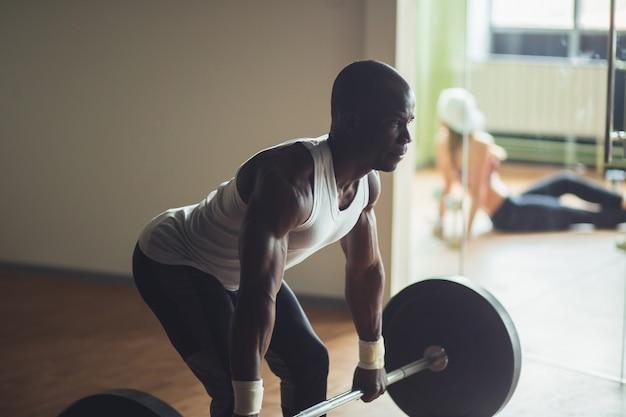 Junger hemdloser mann, der kreuzhebenübung im fitnessstudio tut. nach motivation schreien