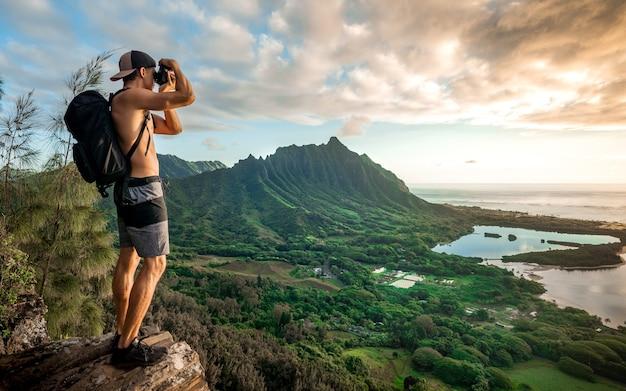 Junger hemdloser mann mit einem rucksack, der auf einem berg steht und ein foto unter einem bewölkten himmel macht