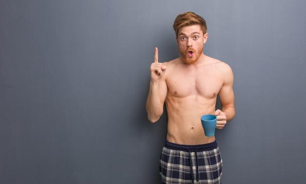 Junger hemdloser rothaarigemann, der eine großartige idee, konzept der kreativität hat. er hält eine kaffeetasse in der hand.