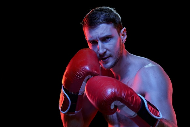 Junger hemdloser sportler in den boxhandschuhen, der seinen rivalen betrachtet, während kampfbereit steht