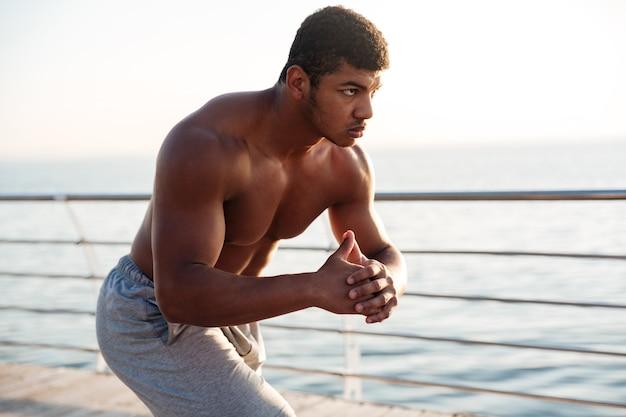 Junger hemdloser sportler macht morgens kniebeugen auf dem pier