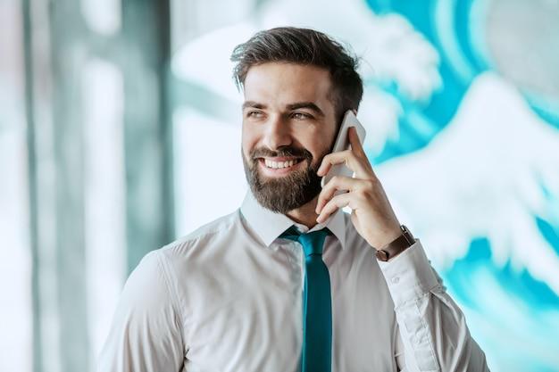 Junger herrlicher lächelnder kaukasischer geschäftsmann in der formellen abnutzung, die am telefon spricht, während er im büro steht.