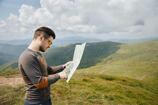 Junger herrlicher mann, der papierkarte in den bergen verwendet