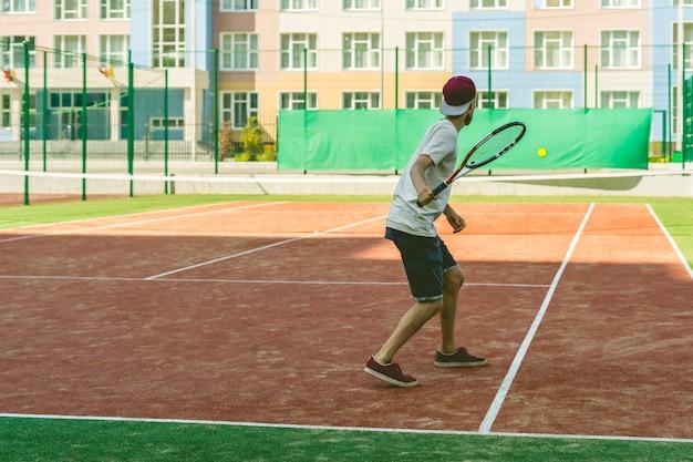 Junger hippie auf dem gericht. der lässige tennisspieler