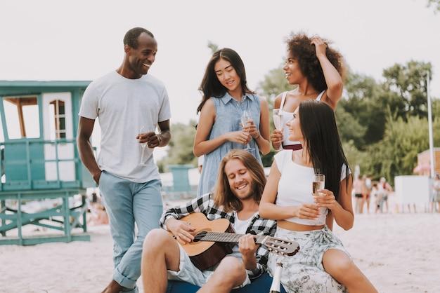 Junger hippie, der gitarren-getränk champagne spielt