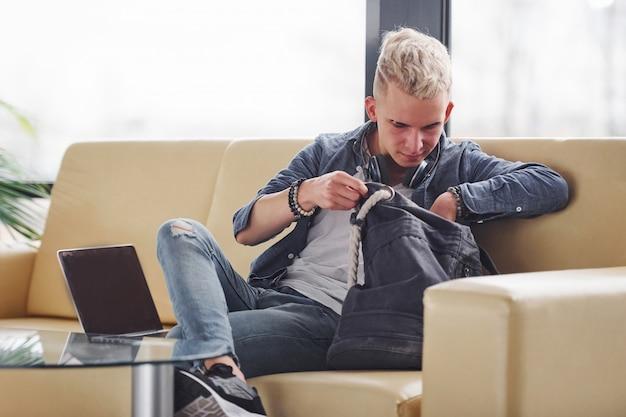 Junger hippie-kerl in der netten kleidung, die auf sofa mit notizblock sitzt