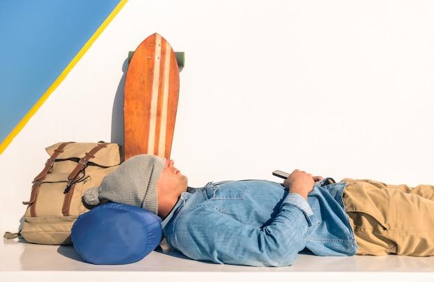 Junger hippie-mann, der einen rest während der fährendurchfahrt hält sein intelligentes mobiltelefon hat