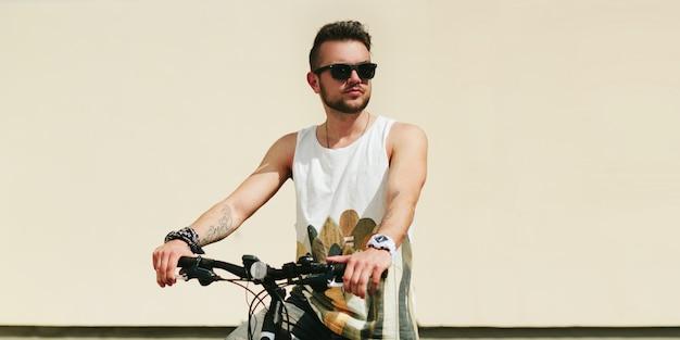 Junger hippie-mann mit fahrrad in der stadt am sonnigen sommertag