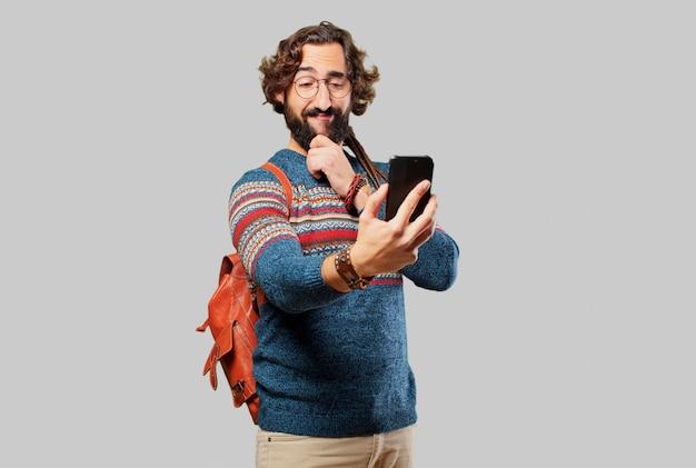 Junger hippiemann mit einem intelligenten telefon