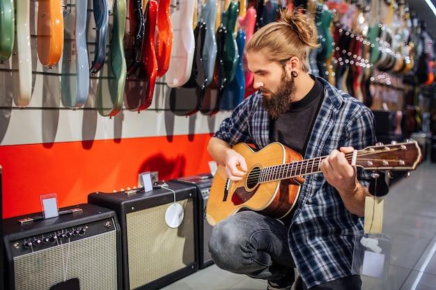 Junger hipster, der auf akustischer gitarre sitzt und spielt. er schaut nach unten. guy ist konzentriert. viele elektronische gitarren und soundkolumnen stehen hinter ihm.
