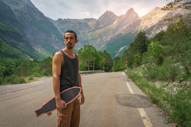 Junger hipster, der ein cooles longboard in der hand hält