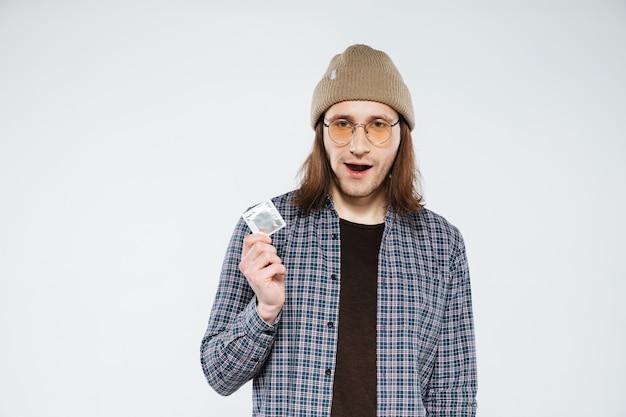 Junger hipster, der kondom hält