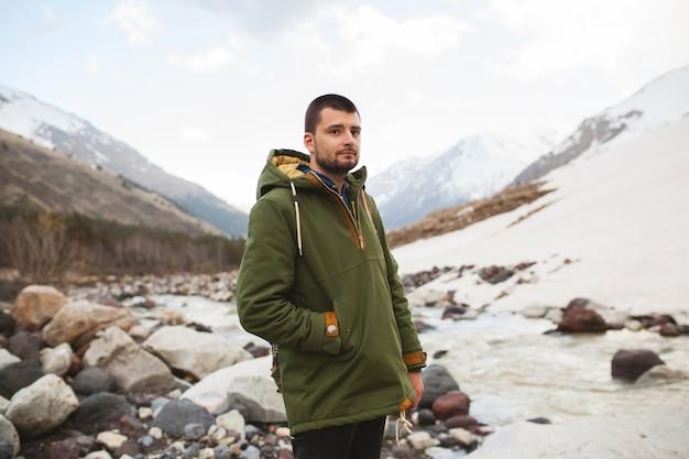 Junger hipster-mann, der durch den fluss, wilde natur, winterferien wandert