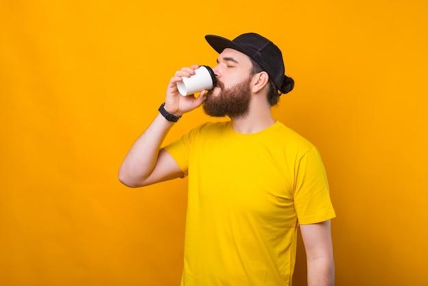 Junger hipster-mann, der kaffee auf gelb trinkt