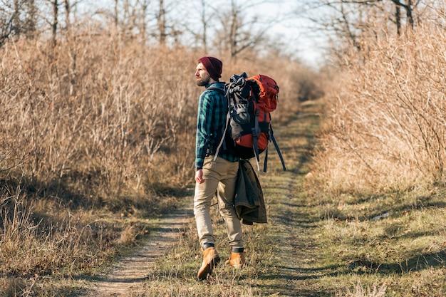 Junger hipster-mann, der mit rucksack im herbstwald mit kariertem hemd und hut reist, aktiver tourist, der natur in der kalten jahreszeit erforscht