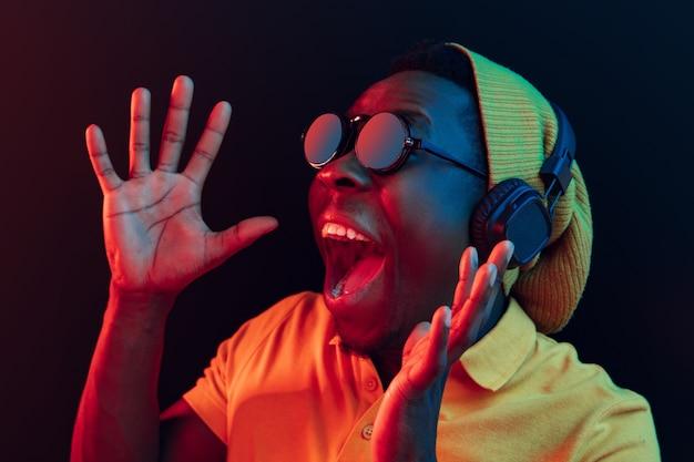 Junger hipster-mann, der musik mit kopfhörern im schwarzen studio mit neonlichtern hört.