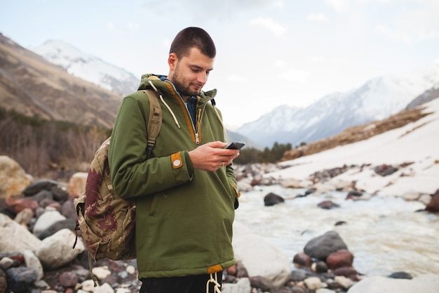 Junger hipster-mann, der smartphone, wilde natur, winterurlaub, wandern verwendet