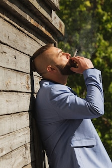Junger hipster mann, der weg von der kamera schaut, während eine zigarette raucht