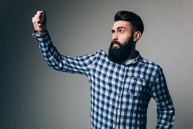 Junger hipster-mann mit langem bart, der selfie mit händen auf bart nimmt, der auf grauer wand steht