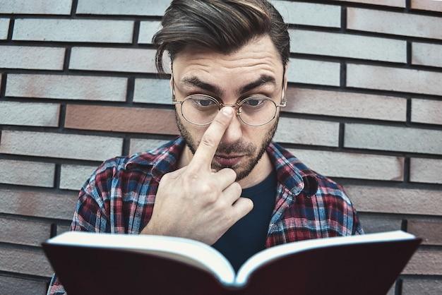 Junger hipster-typ, der brillen trägt, die ein buch oder ein notizbuch auf ziegelwandoberfläche lesen