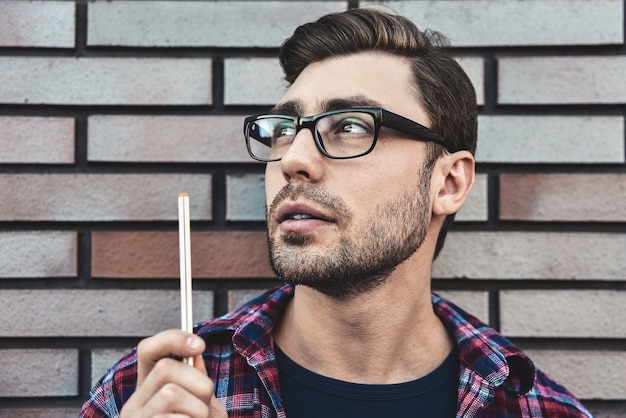 Junger hipster-typ, der brillen trägt, die ein buch oder ein notizbuch lesen, machen einige notizen und ideen auf backsteinmauerhintergrund.