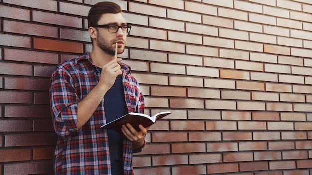 Junger hipster-typ, der brillen trägt, die ein buch oder ein notizbuch lesen, machen einige notizen und ideen auf ziegelwandoberfläche