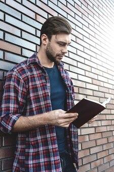 Junger hipster-typ, der ein buch oder ein notizbuch auf ziegelmaueroberfläche liest