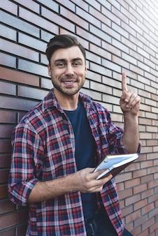 Junger hipster-typ, der ein buch oder ein notizbuch liest und eine idee auf ziegelmaueroberfläche hat