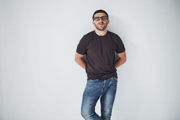Junger hipster-typ, der eine brille trägt, die glücklich lokalisiert auf weiß lacht
