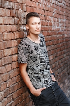Junger hipster-typ in einem schwarzen hemd, das nahe roter backsteinmauer mit graffiti steht