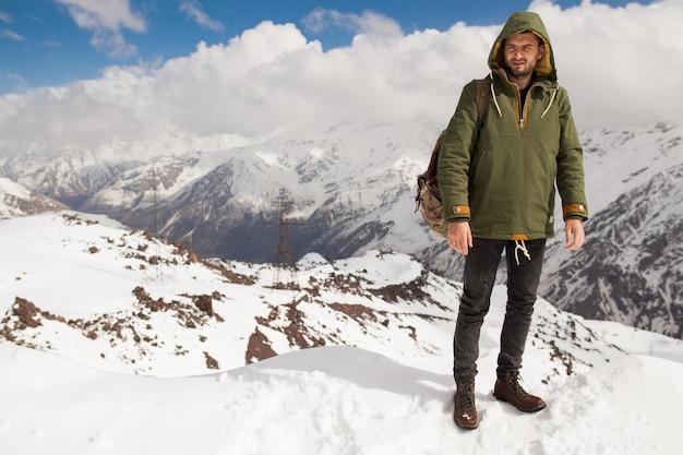 Junger hipstermann, der in den bergen wandert, winterferienreisen
