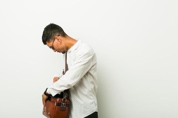 Junger hispanischer geschäftsmann, der ein plakat hält