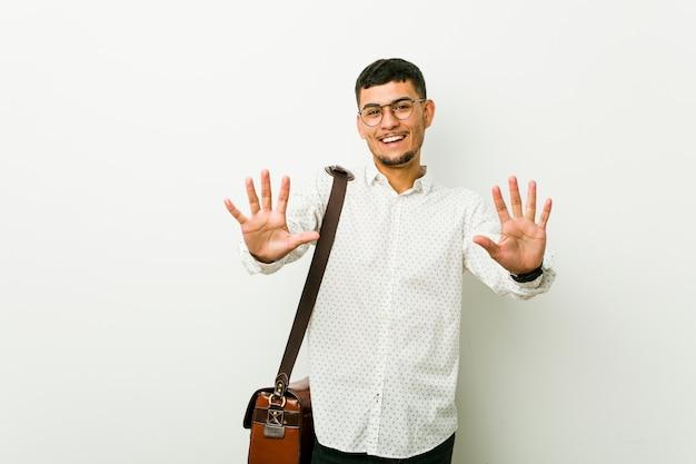 Junger hispanischer lässiger geschäftsmann, der nummer zehn mit den händen zeigt.