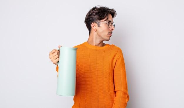 Junger hispanischer mann auf der profilansicht, der nachdenkt, sich vorstellt oder träumt. thermos-konzept