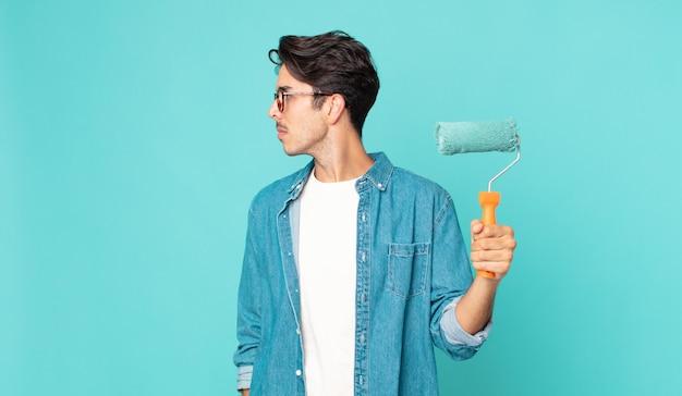 Junger hispanischer mann auf profilansicht, der nachdenkt, sich vorstellt oder träumt und einen farbroller hält