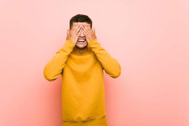 Junger hispanischer mann bedeckt augen mit den händen und lächelt breit, auf eine überraschung wartend.