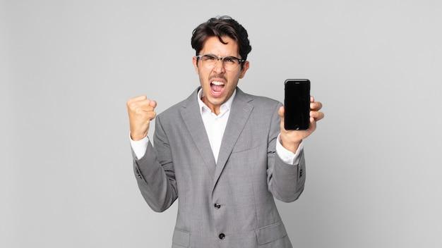 Junger hispanischer mann, der aggressiv mit einem wütenden ausdruck schreit und ein smartphone hält